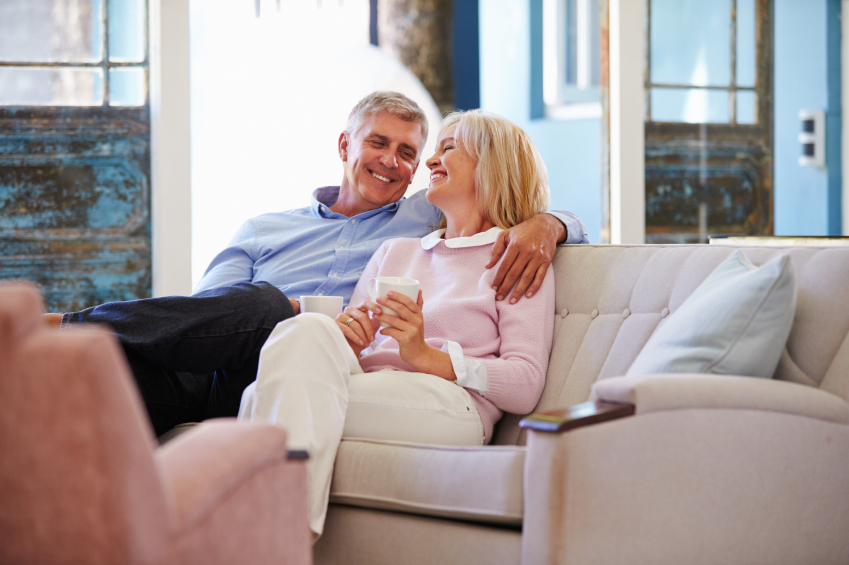 Mature Couple At Home Relaxing In Lounge With Hot Drink