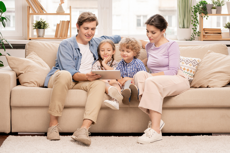Parents reading book to children on couch