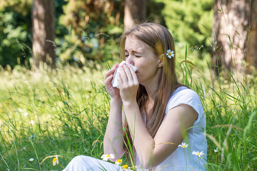 young girl sitting in grass sneezing