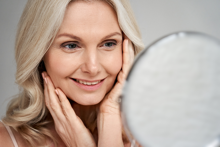 blonde woman looking at face in mirror