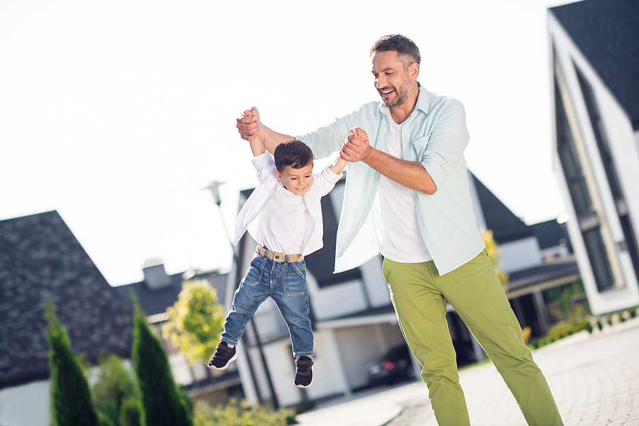 dad swinging young son with his arms
