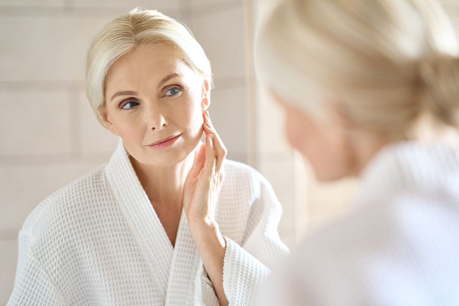 pretty blonde mid age woman looking at face in mirror
