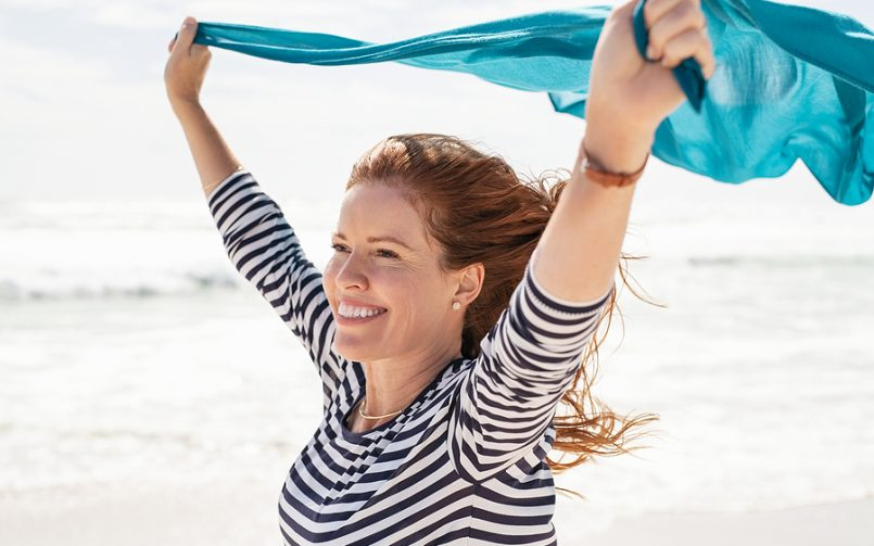 red hair woman smiling at beach holding scarf up in wind