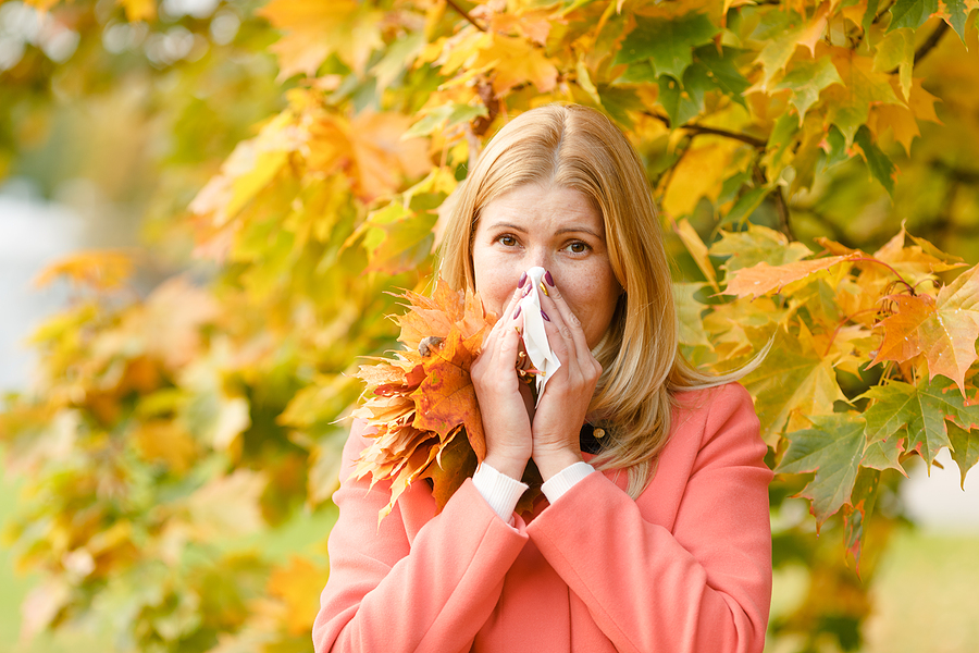 blonde woman kleenex in front of fall tree