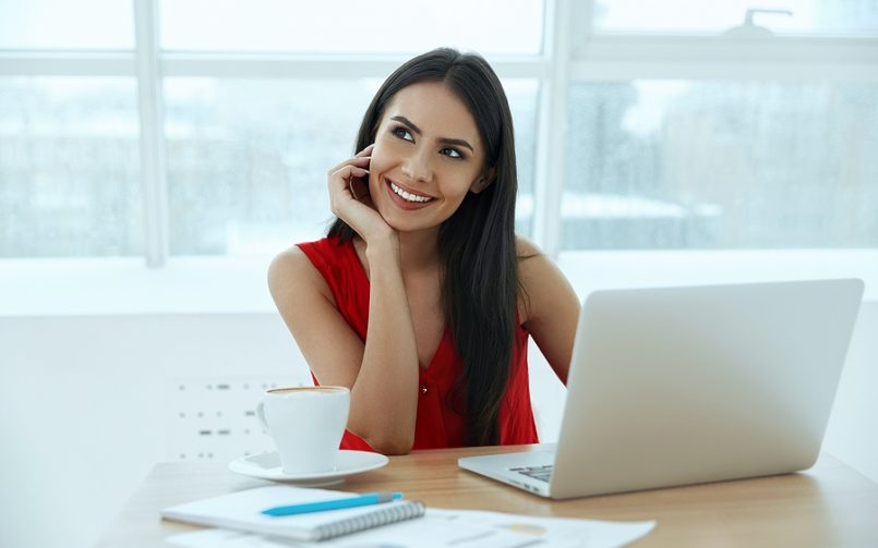 dark hair woman in red top thinking at desk